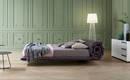 Кровать, стеганное основание которой скатывается в подголовник
