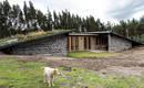 Каменный дом с травянистой крышей, встроенный в сельский пейзаж