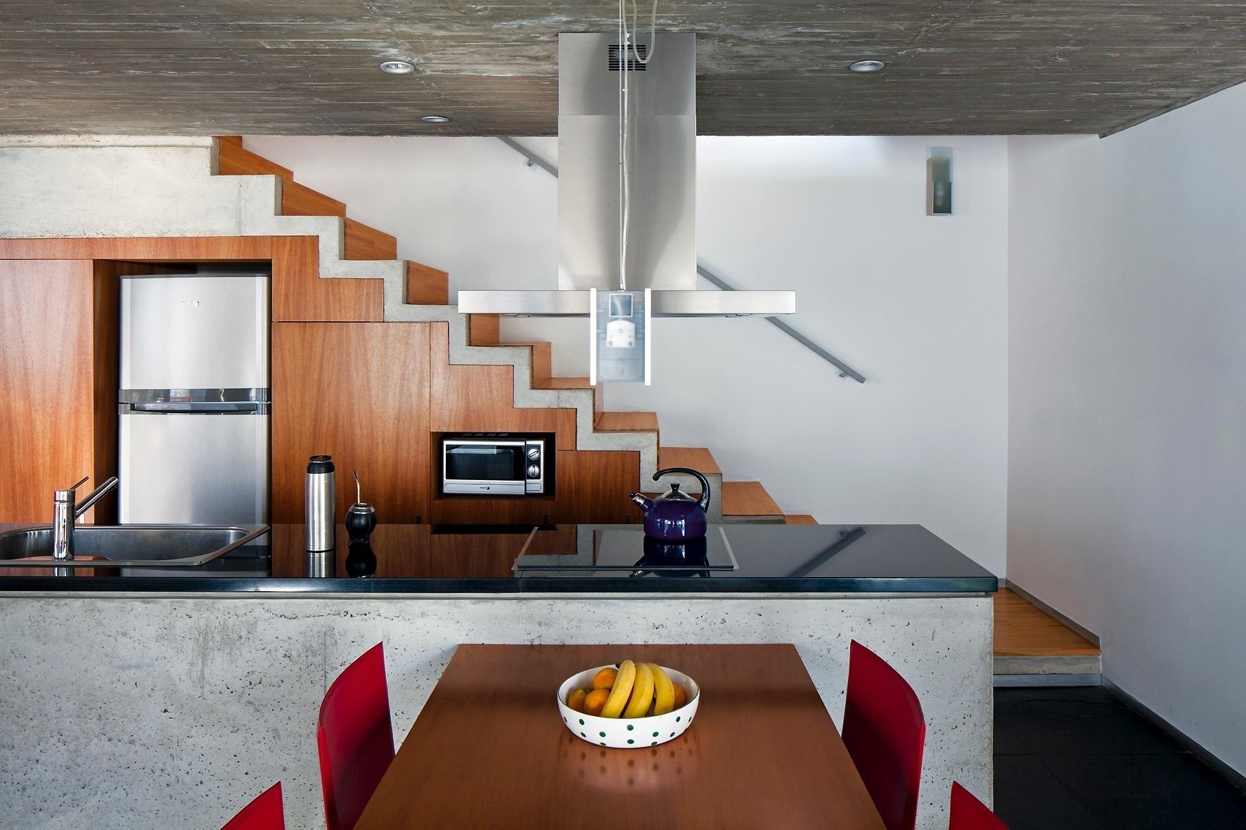o-fundo-do-terreno-sul-concentra-circulacao-escadas-para-o-pavimento-superior-intimo-e-encaixa-a-cozinha-embutindo-marcenaria-para-armarios-forno-e-geladeira-sob-os-degra