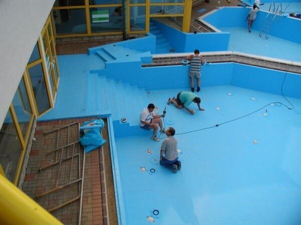 Люди, которые прокладывают гидроизоляцию бассейна