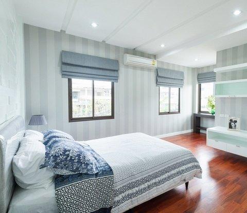 Светлая спальня в белом цвете и с коричневым полом