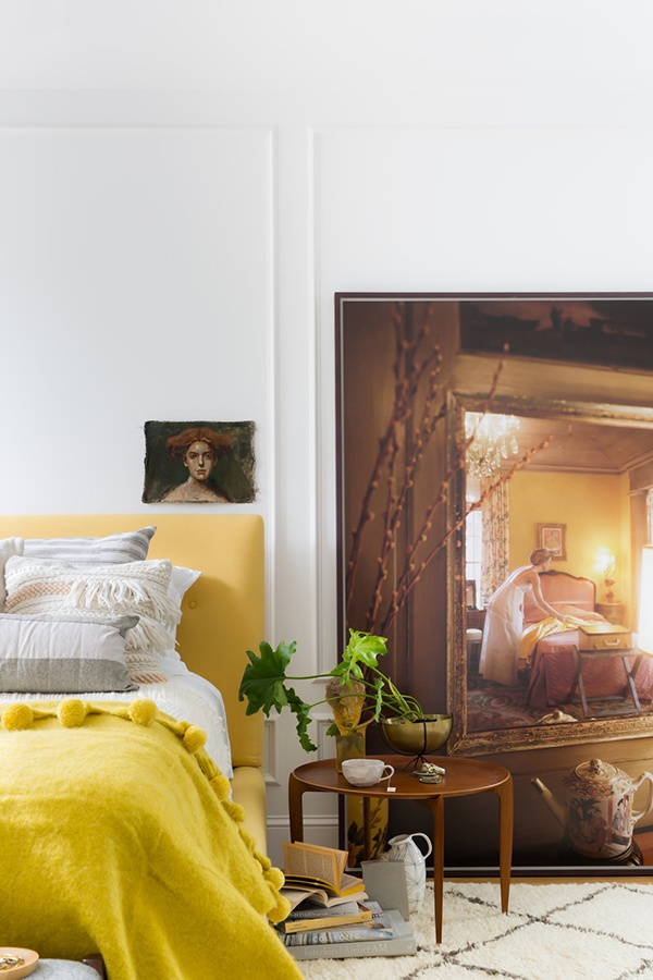 09-the-master-bedroom-raises-the-mood-with-cool-artworks-and-a-sunny-yellow-upholstered-bed