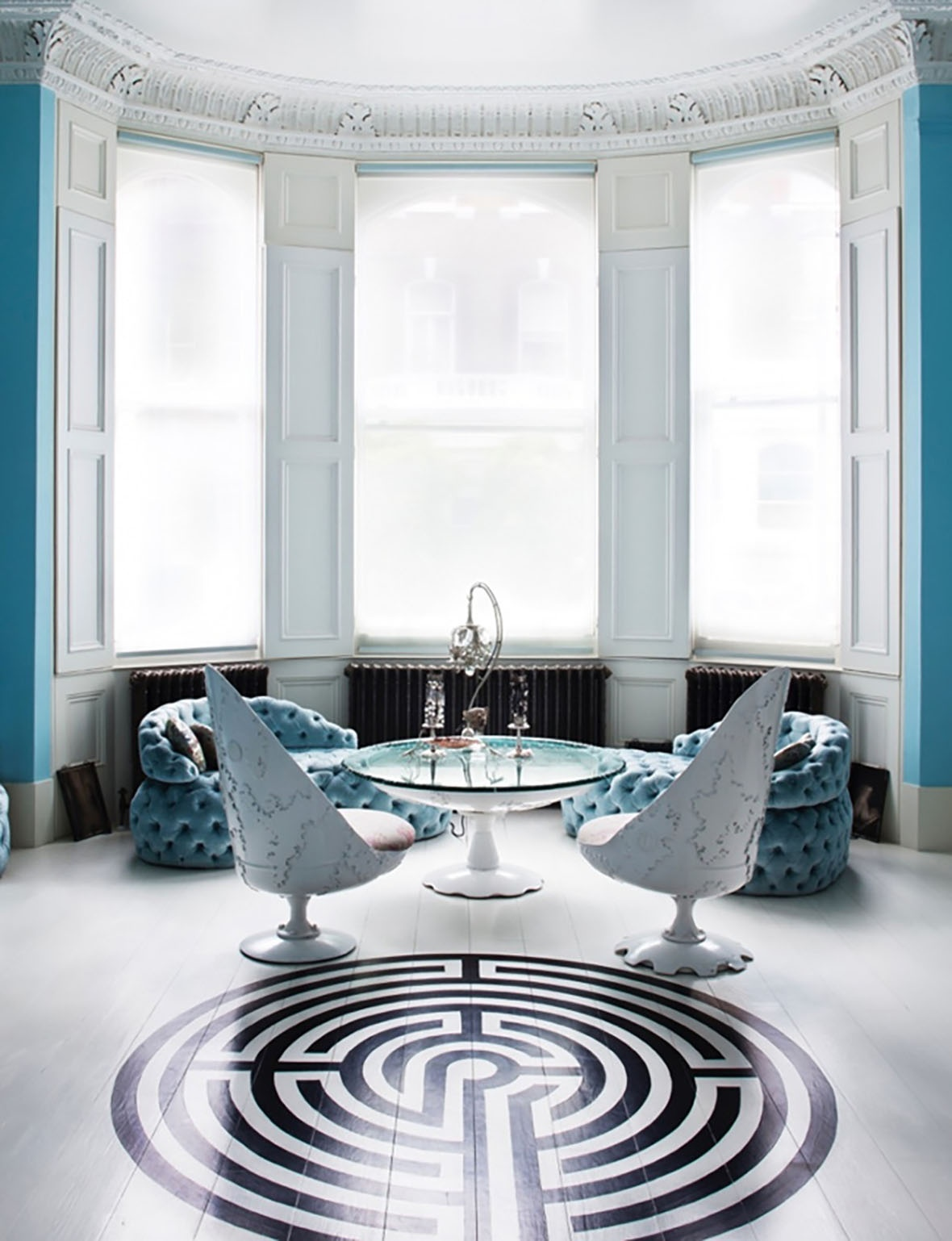 04-matching-blue-chairs-are-placed-by-the-large-windows-and-theres-a-cool-geo-pattern-on-the-floor