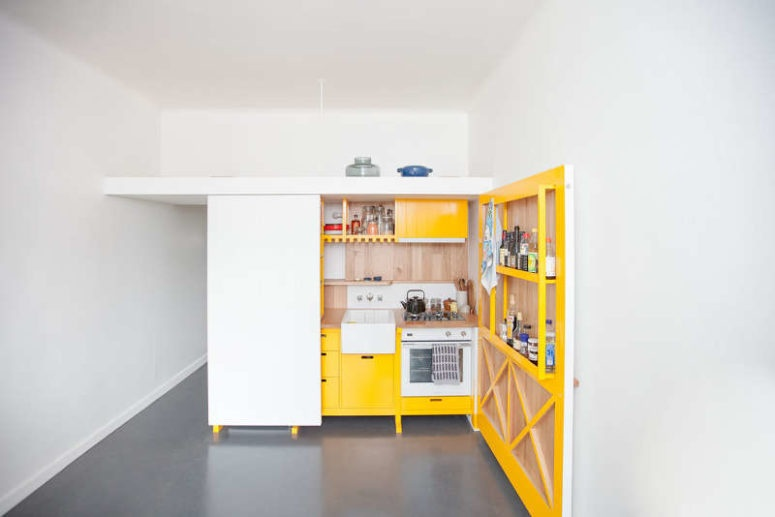 01-this-chic-mini-kitchen-was-built-for-a-studio-apartment-and-features-bold-yellow-cabinets-and-lots-of-storage-space-775x517_01