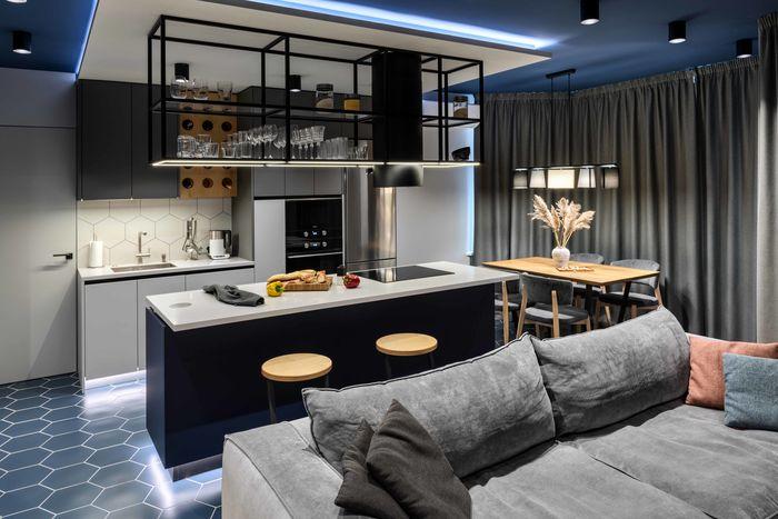 Вся зона кухни выделена подсветками на 3х уровнях: подсветка цоколя, для создания парения и расслабляющей атмосферы в студио, рабочая подсветка и «парящий» короб над зоной кухни.
