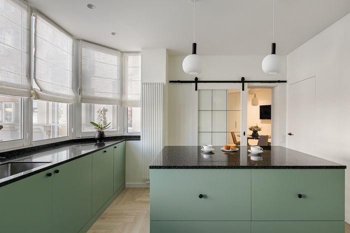 """Фасады кухни нежно-зеленого цвета подчеркнуты темной столешницей и ручками """"пуговками""""."""