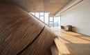 Поразительная изогнутая стена возвышается над тремя историями дома