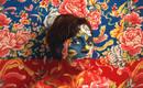 Автопортрет против яркого цветочного текстиля