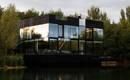 Стеклянный дом на озере создает впечатление плывущего по воде